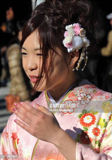 A young Japanese woman wearing a traditional kimono and kanzashi hair accessory poses for photos at the MeijiJingu shrine in the Harajuku district of...