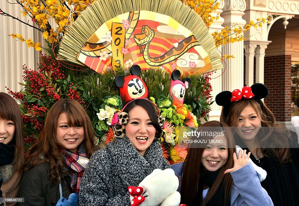 Young Japanese women pose in front of a New Year's decorations with picture of a snake to mark the Year of the Snake in the Chinese zodiac, on display at Tokyo Disneyland in Urayasu, suburban Tokyo on January 1, 2013. Thousands of people visited the theme park to mark the start of the New Year's holiday, the biggest one of the year in Japan. The 'Year of the Snake' will be marked across much of the rest of East and Southeast Asia in mid-February, 2013 at the Lunar New Year holidays. AFP PHOTO / Yoshikazu TSUNO