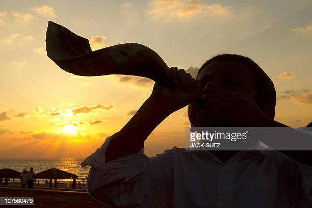 A young Jewish boy blows the shofar horn along the beach in the coastal city of Ashdod during the ritual of Tashlich on September 29 2011 Jews...