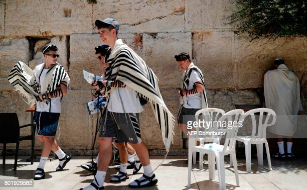 Young Jewish men pray at the men's section of the Western Wall the most holy site where Jews can pray in Jerusalem's Old City on June 27 2017...