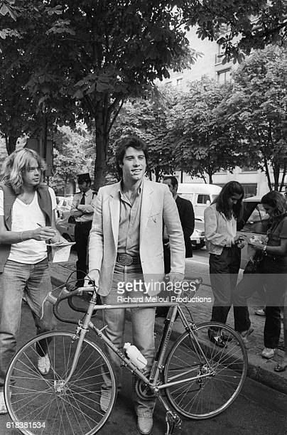 A young John Travolta is approached by fans while in Paris