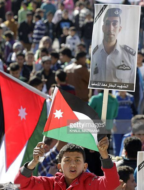 A young Jordanian waves a national flag holding a placard on February 5 2015 in the capital Amman during a rally against the Islamic state group and...