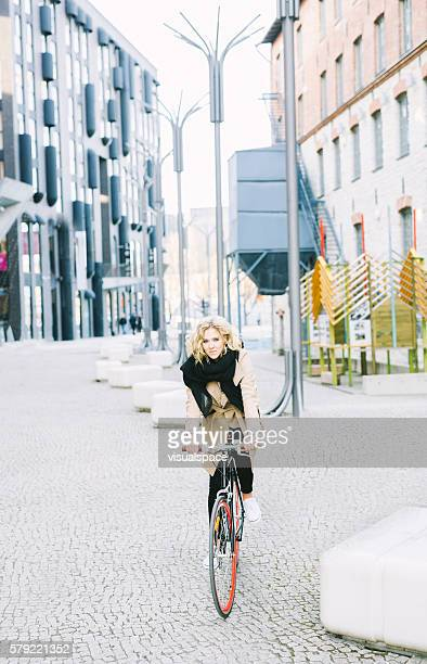 Young Joyful Woman Riding A Bicycle In Modern Shopping District
