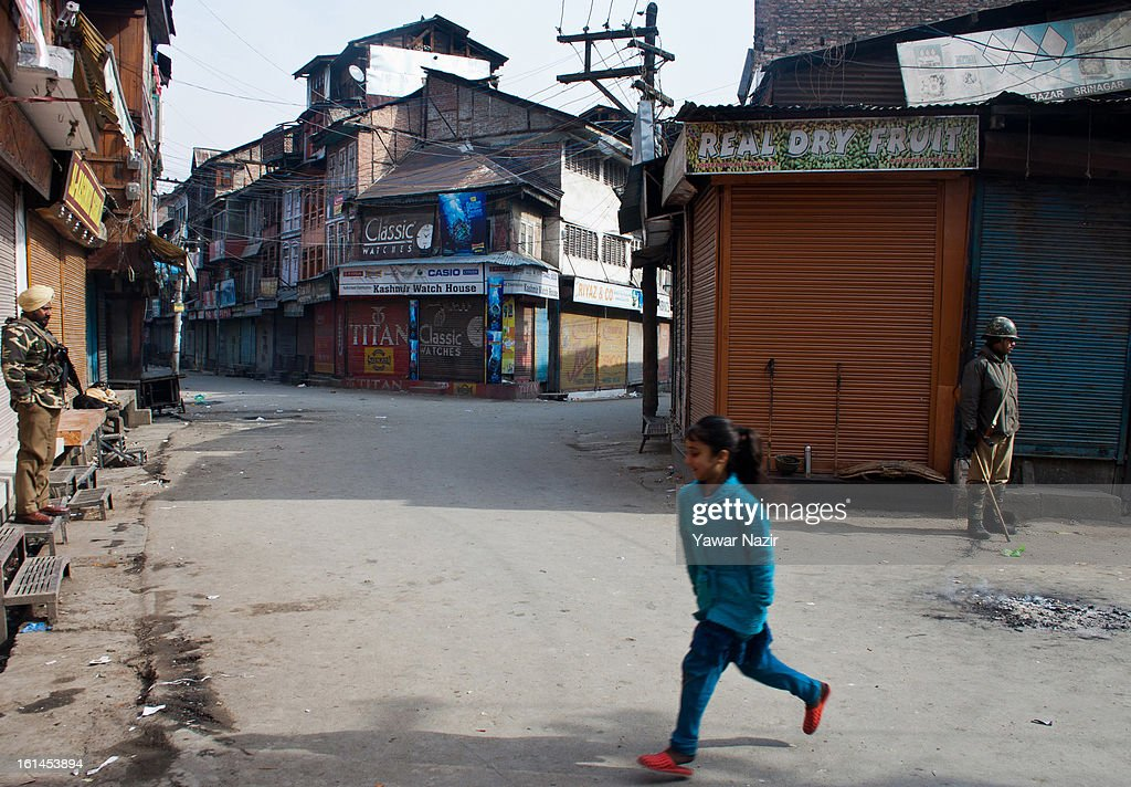A young Kashmiri Muslim girl dashes across a road Indian paramilitary soldiers stand guard during a curfew on the third consecutive day, following the execution of alleged Indian parliament attacker Mohammad Afzal Guru on February 11, 2013 in Srinagar, the summer capital of Indian Administered Kashmir, India. Afzal Guru, from Sopore town in the north of Kashmir, was hung on February 09 for his role in the 2001 Indian parliament attack which left 14 dead. The hanging has further strained relations between India - who blamed the attack on 'Pakistan backed' militant group Jaish-e-Mohammed - and neighbouring Pakistan and has seen an military increase from both along the border.