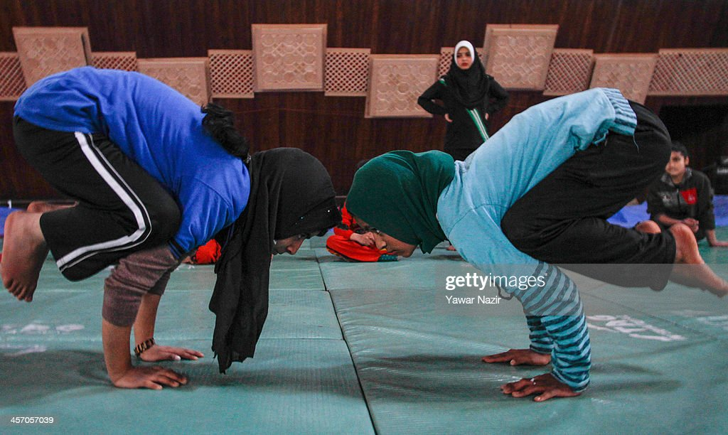 Young Kashmiri Muslim girls learn to balance on hands from a coach inside indoor stadium on December 16, 2013 in Srinagar, the summer capital of Indian administered Kashmir, India. As the number of crimes against women has risen in the region, girls from different age groups and backgrounds have taken up martial arts and other self defence courses to thwart attackers. Many believe after the barbaric rape and murder of a para-medic student last year on this day in the Indian capital of New Delhi, women in the Muslim majority state have taken to various martial arts forms like Thang-ta, a weapon-based Indian Martial art for protection.