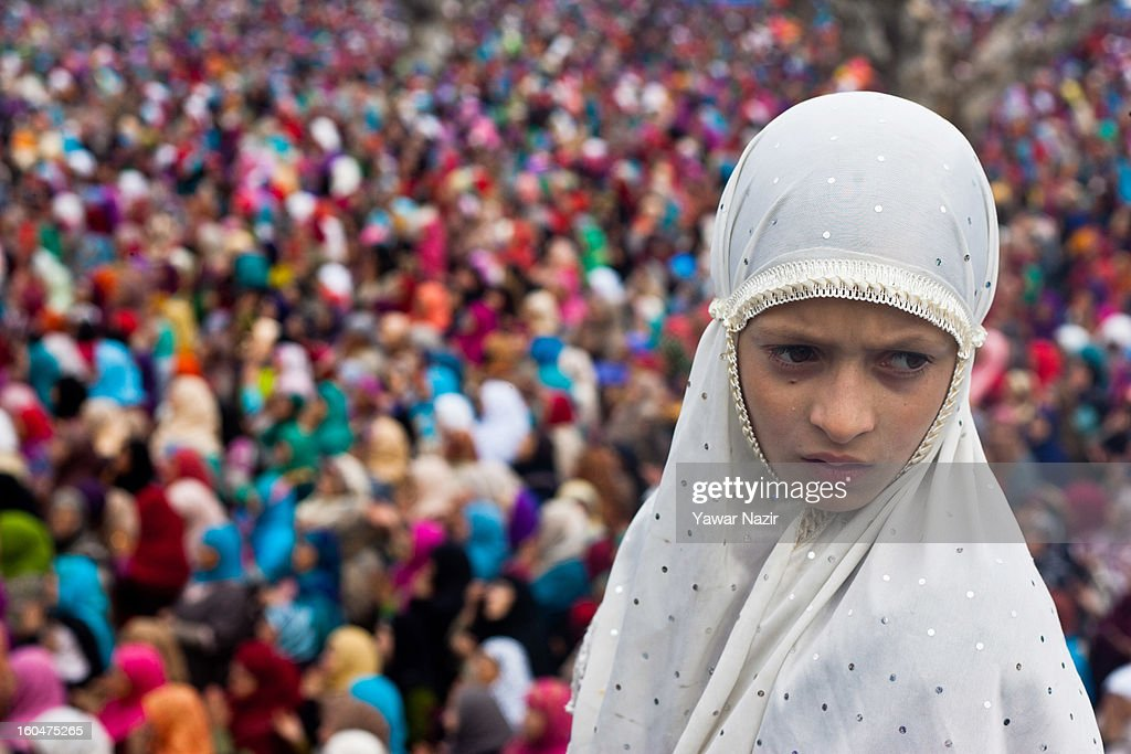 A young Kashmiri Muslim looks off as Muslim women pray at Hazratbal shrine on the Friday following Eid-e-Milad , or the birth anniversary of Prophet Mohammad on February 01, 2013 in Srinagar, the summer capital of Indian administered Kashmir, India. Thousands of Muslims from all over Kashmir visit the Hazratbal shrine in Srinagar to pay obeisance on the Friday following Eid-e-Milad , or the birth anniversary of Prophet Mohammed. The shrine is highly revered by Kashmiri Muslims as it is believed to house a holy relic of the Prophet Mohammed. The relic is displayed to the devotees on important Islamic days such as the Eid- Milad when Muslims worldwide celebrate.