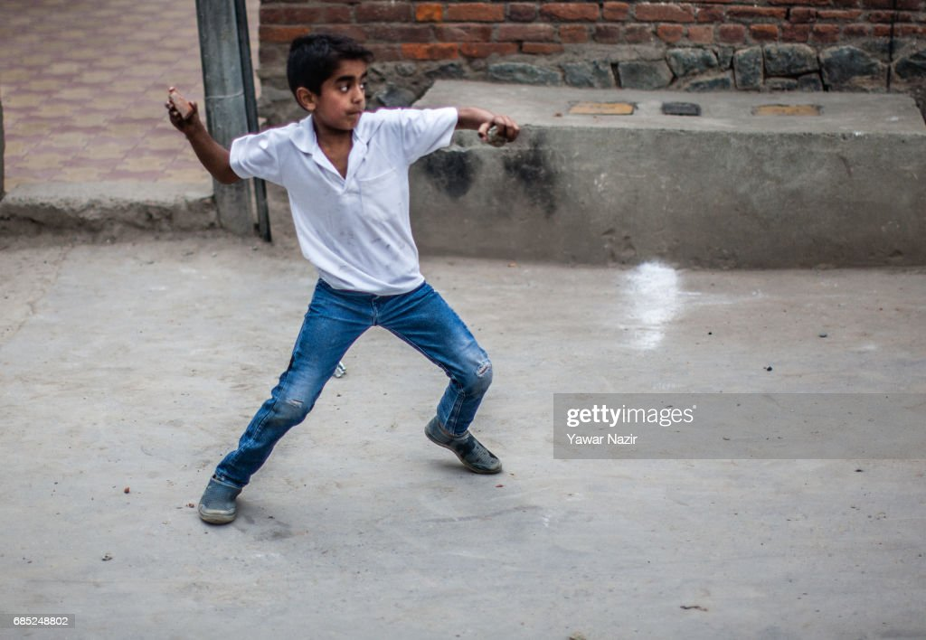 A young Kashmiri Muslim protester throws a stone at Indian government forces during an anti India protest on May 19, 2017 in Srinagar, the summer capital of Indian administered Kashmir, India. Indian government forces used teargas shells to disperse dozens of Kashmiri Muslim protesters who were throwing stones at them during an anti Indian protest in the Old City of Srinagar, after Friday prayers.