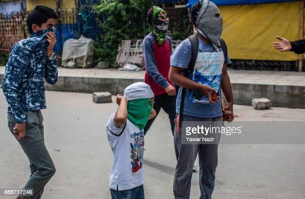 A young Kashmiri Muslim protester ties his mask before throwing stones at Indian government forces during a protest against Indian government and...