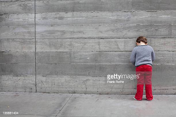 young kid leans against a big wall