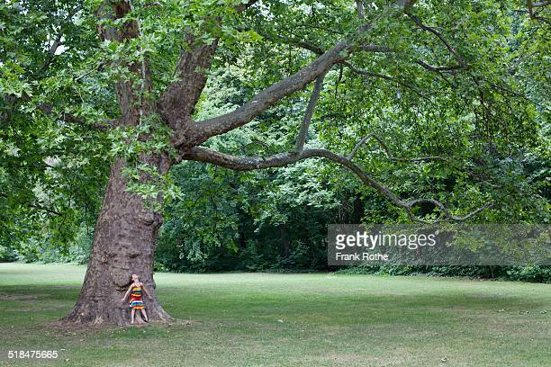 young kid leans against a very big and old tree
