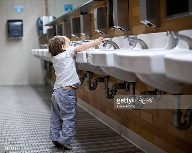 young kid plays with water from a tap