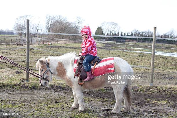 young kid ridin a pony and smiles into the camera