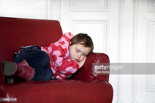 young kid sleeps in a red armchair