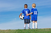 A rear view photo of two kids on a youth recreation league soccer team. Diverse little boys