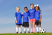 A portrait of four young kids on a youth recreation league soccer team