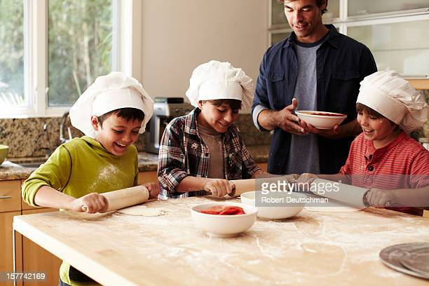 Young kids preparing pizza.