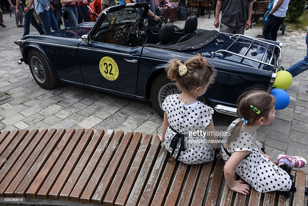 Young Kosovar girls sit next to a vintage car displayed during the 11th Old Timers Fest on May 29, 2016 in Prizren. / AFP / ARMEND