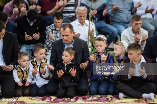 Young Kosovo Muslims attend the Eid alFitr prayer near the Sulltan Mehmet Fatih mosque in Pristina on June 25 2017 Eid alFitr festival marks the end...