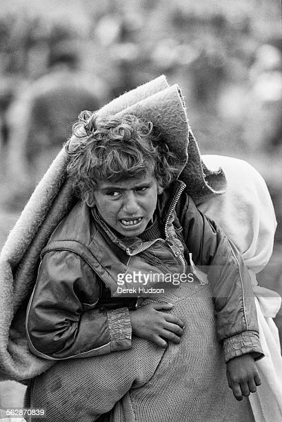 A young Kurdish boy is carried is carried by his mother at Isikveren camp where his family fled to after being persecuted by the Republican Guard in...