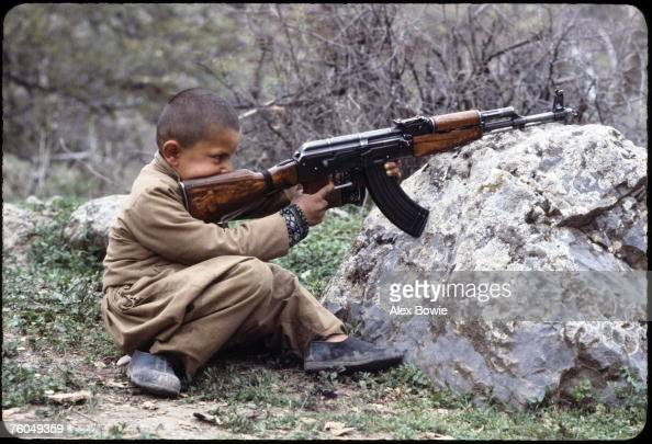A young Kurdish boy learns how to handle his Peshmerga father's AK47 assault rifle in northern Iraq 12th May 1979