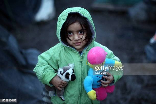 A young Kurdish girl holds her toys as she stands in the mud in a new migrant camp on January 6 2016 in Dunkirk France Thousands of migrants continue...
