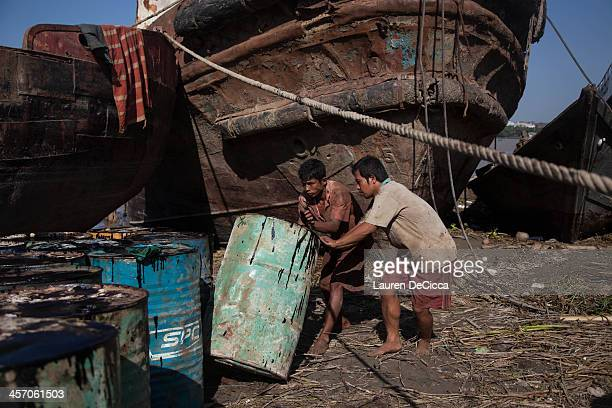 Young laborers stack recycled oil drums weighing 240kg on the banks of the Irrawaddy River in the Dala township of Yangon on December 16 2013 in...