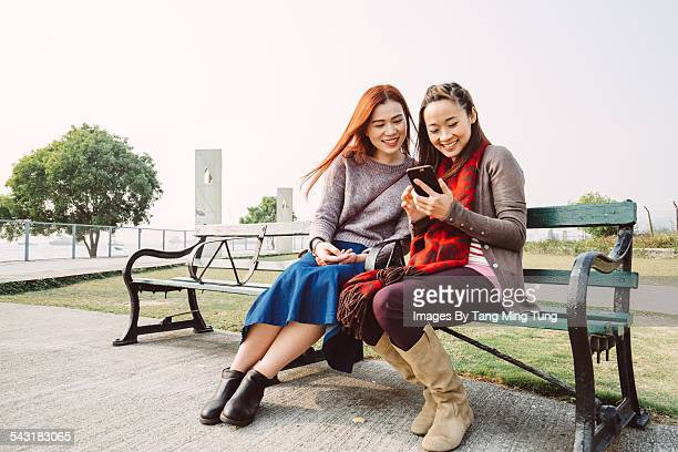 Young ladies using smartphone joyfully in park