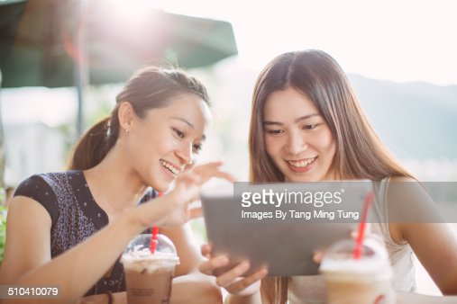 Young ladies using tablet joyfully in cafe
