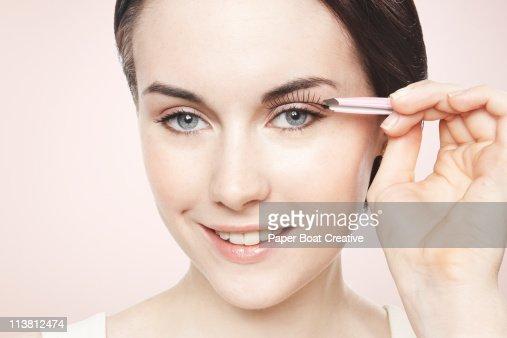 Young lady applying fake eyelashes on one eye