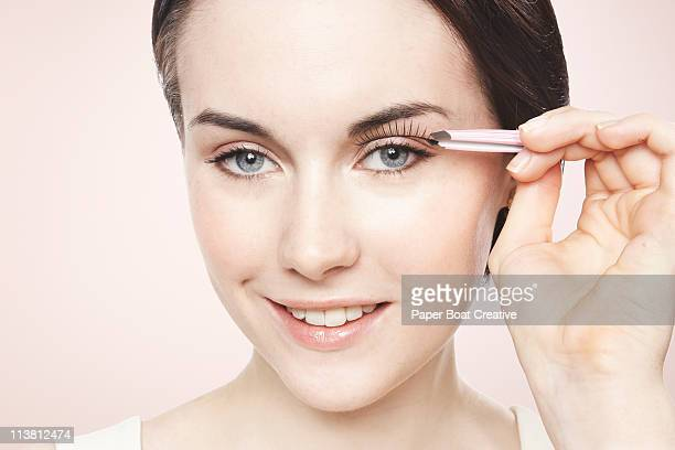 Young lady applying fake eyelashes on one eye