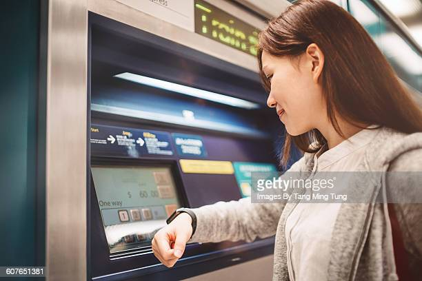 Young lady buying ticket at vending machine