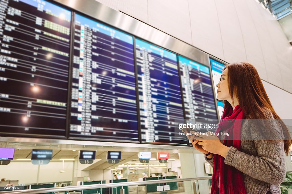 Young lady checking flight status board at airport