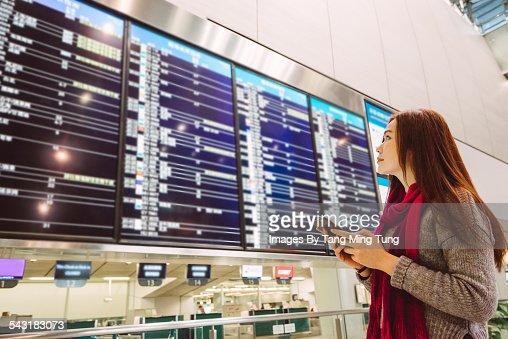 Young lady checking flight status board at airport