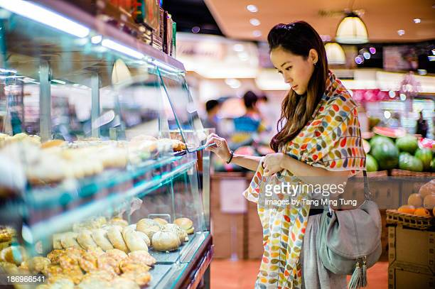 Young lady choosing breads in the bakery
