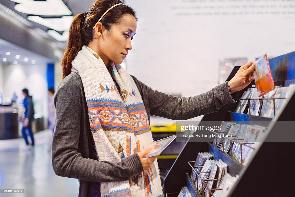 Young lady choosing cd records in record store