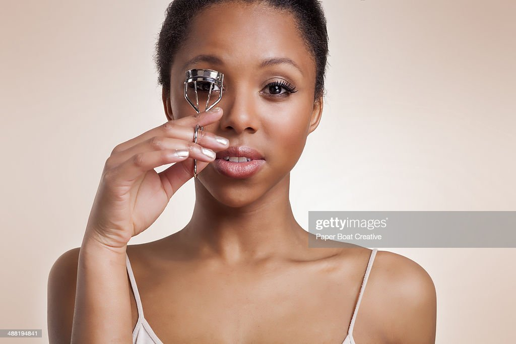 Young lady curling her eyelashes with a curler : Stock Photo