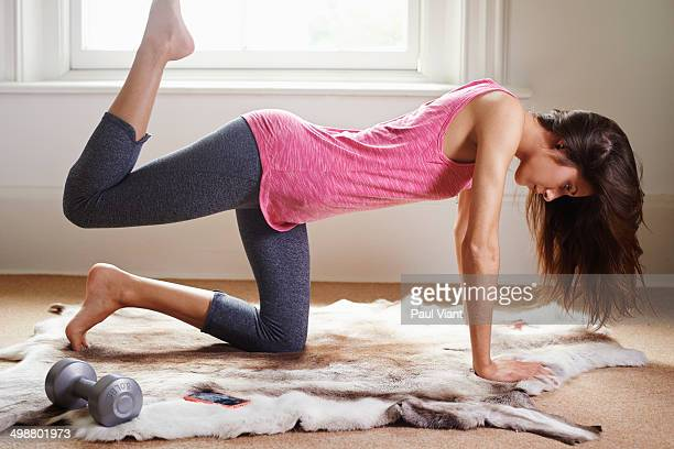 Young lady doing exercises in bedroom