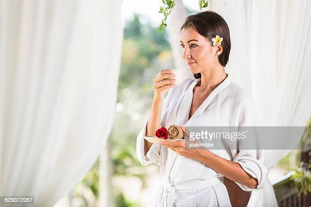 Young lady enjoying her cup of tea after massage