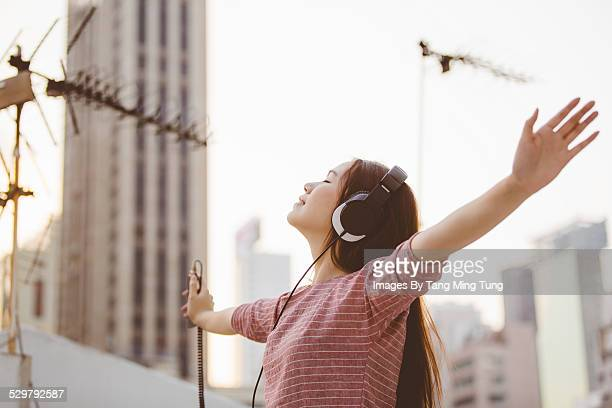 Young lady enjoying listening to music at rooftop