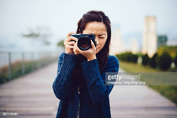 Young lady focusing a camera at the dock