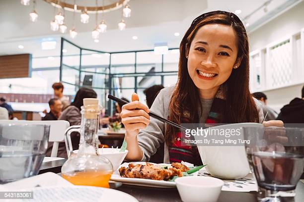 Young lady having meal in restaurant joyfully
