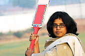 A young lady holding a cricket bat
