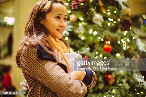 Young lady holding a gift in front of Xmas tree