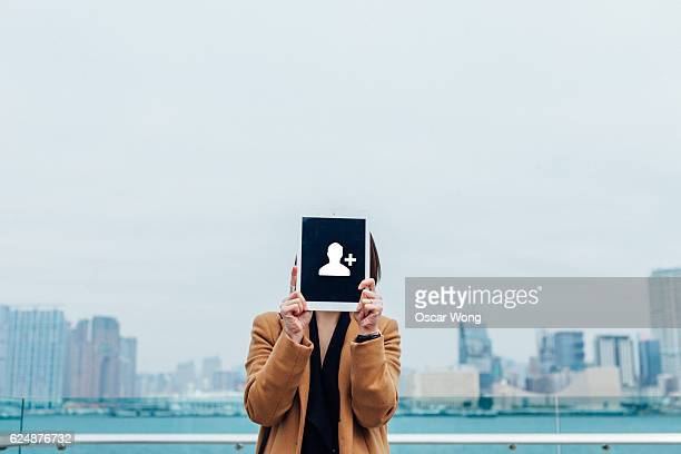 Young lady holding digital tablet with an add friend icon