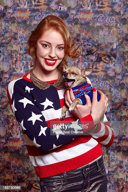 young lady holding her pet chihuahua who's yawning