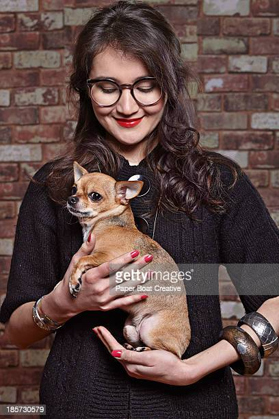young lady holding her pet dog in her hands