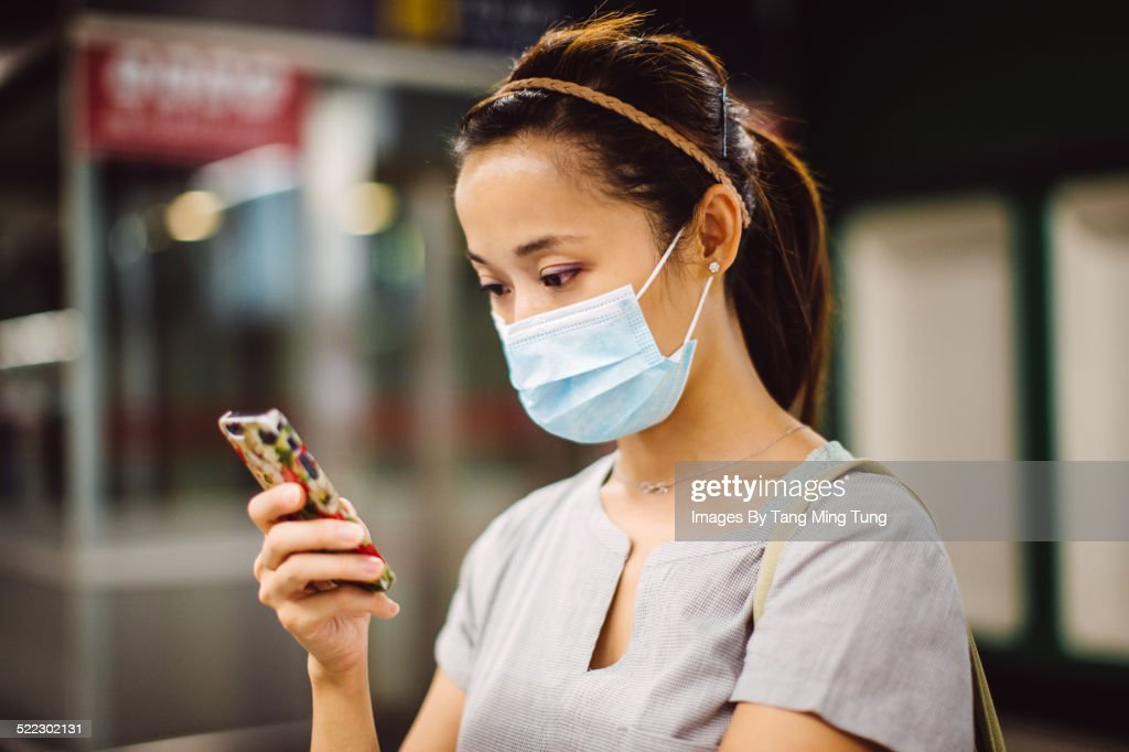Young lady in mask using smartphone on platform