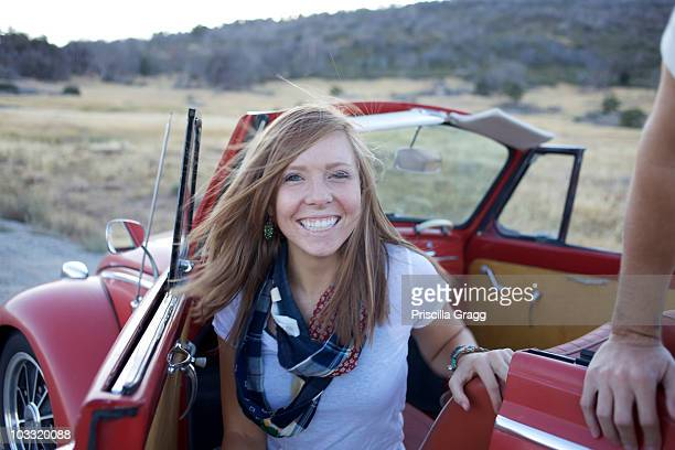 Young lady inside her retro car parked by the road looks at the camera and smiles.