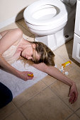 Young lady laying on bathroom floor next to pills