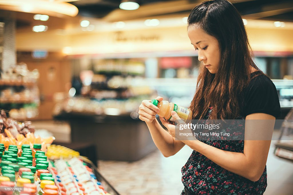 Young lady look at nutrition labels in supermarket : Stock Photo